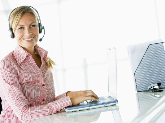 Woman-using-laptop-wearing-telephone-headset-mt2015