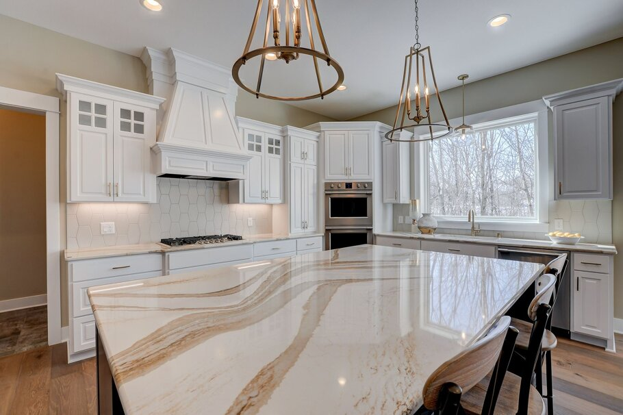 Brittanicca Gold Cambria Quartz Kitchen Countertops with White Wood Cabinets, Wood Floors, and Bar Stools
